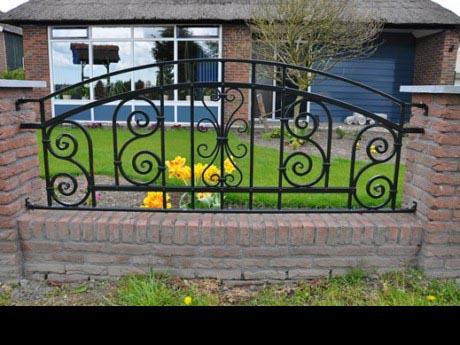 Mooi geklonken hek tussen gemetselde palen.