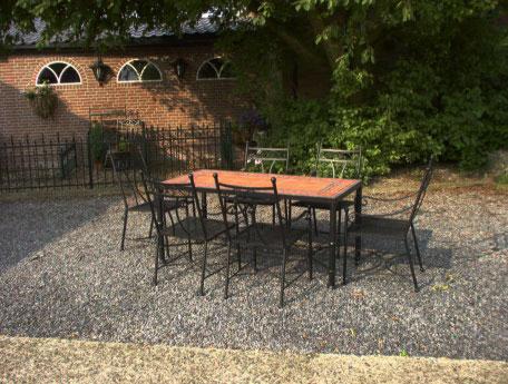 Smeedijzeren tuintafel met stoelen.
